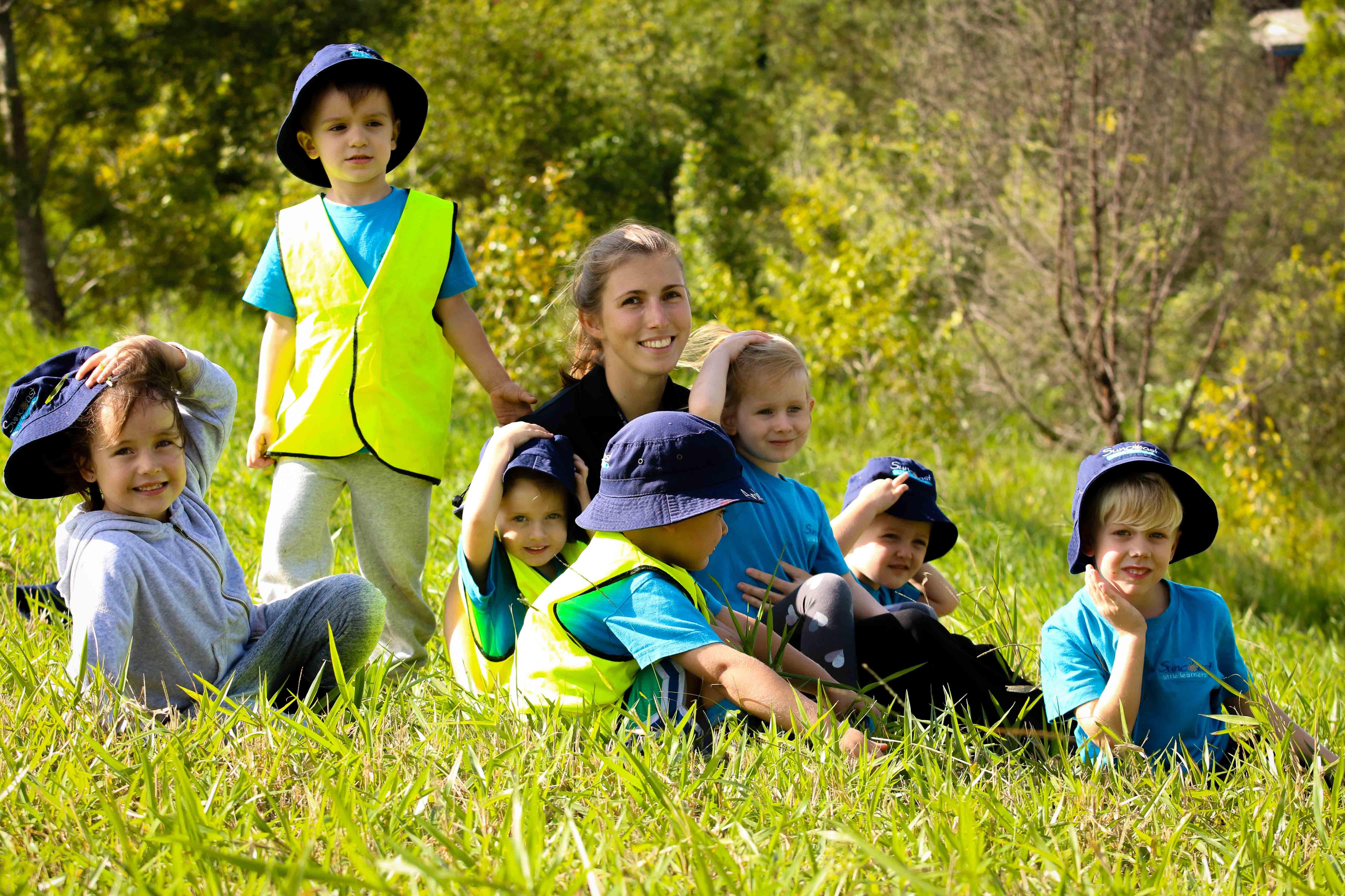 Teacher and students in field at Bush Kindy - Suncoast Little Learners