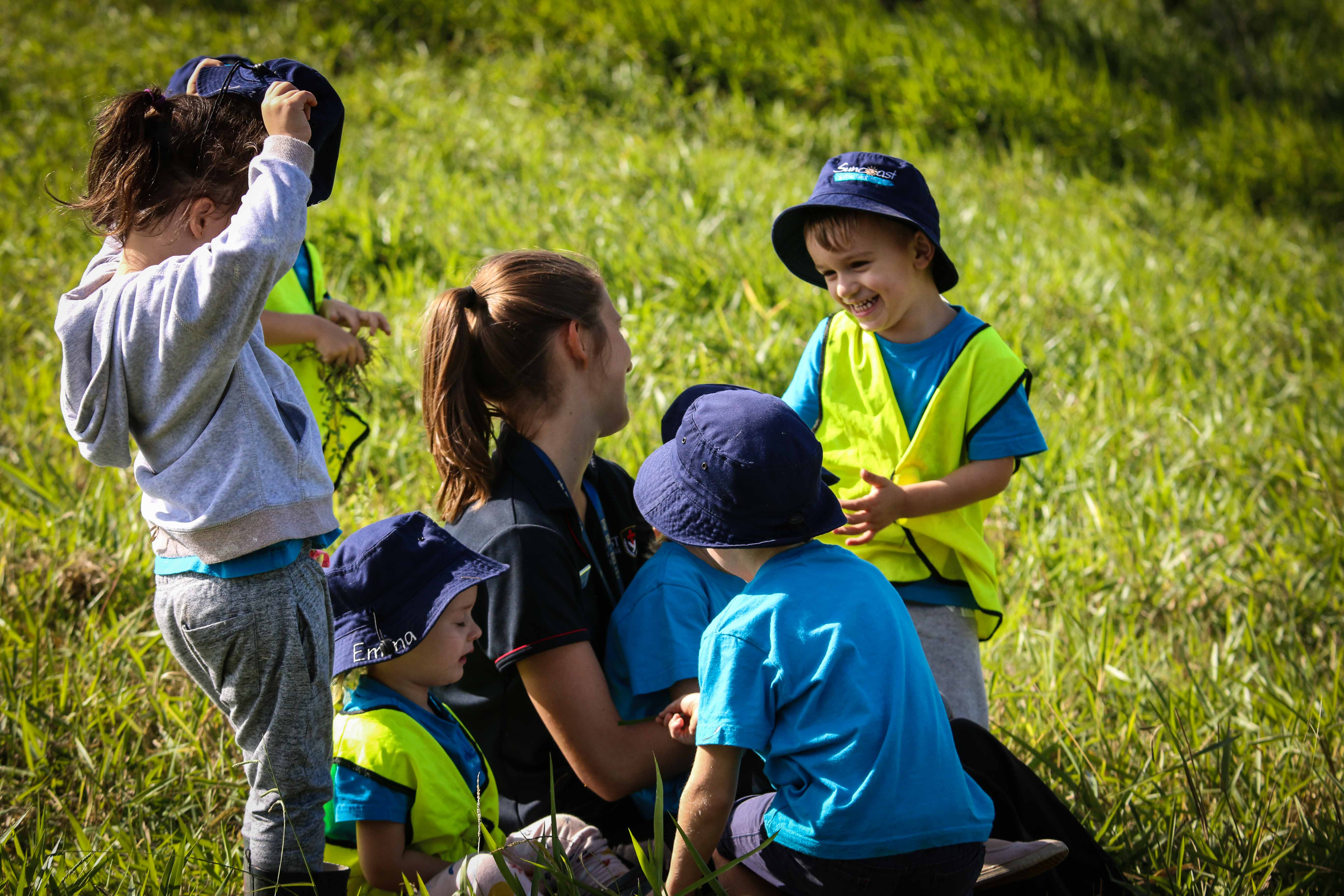 Childcare educator with smiling child in field during Bush Kindy at Suncoasst Little Learners