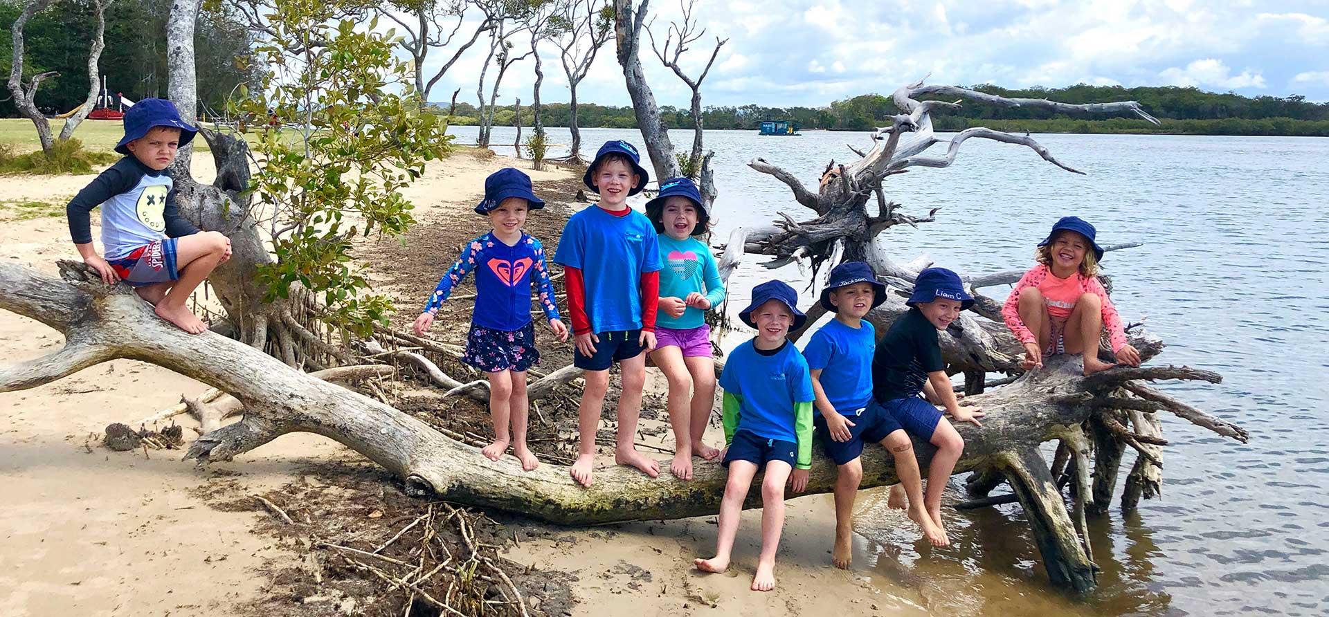 Beach Kindy - a group of Suncoast Little Learners on log at beach on Chambers Island